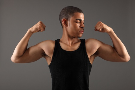 Bicep muscles on fit body of a handsome young african american man showing off his physique wearing black vest, shot against grey background. photo