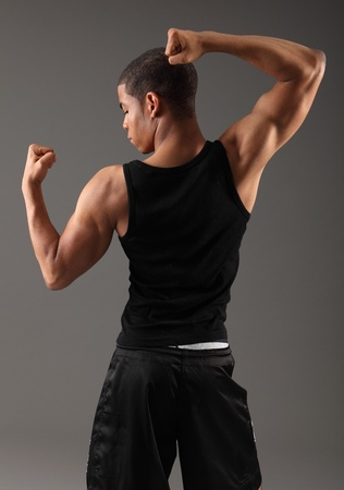 off the shoulder: Deltoid shoulder and bicep muscles on fit body of a handsome young african american man, taken from behind showing off his physique wearing black vest, shot against grey background.