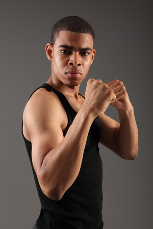 Fist clenched and bicep muscles on fit body of a handsome young african american man, showing off his physique in an aggressive pose wearing black vest, shot against grey background. photo