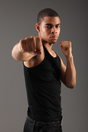 Punch with clenched fist of a handsome young african american man, showing off his muscles and fit physique in an aggressive fight pose wearing black vest, shot against grey background. photo