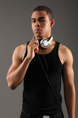 physique: Music DJ handsome young african american man, showing off his muscles and fit physique wearing black vest with headphones around his neck, shot against grey background.