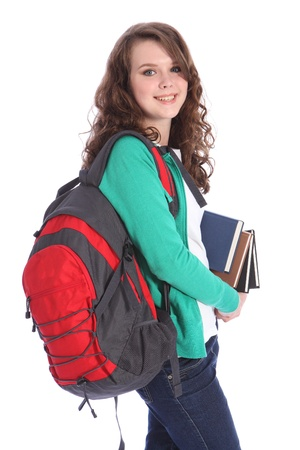 High school teenager girl with long brown hair wearing green jumper and red school backpack carrying education books with big happy smile. Studio shot against white background. photo