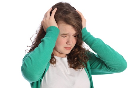 Head in hands for young teenager girl looking stressed and frightened with eyes closed. She is wearing a green hoodie and a sad expression on her face. photo