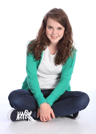legged: Sitting cross legged on floor a beautiful high school teenager girl with long brown hair wearing blue jeans and green jumper with big happy smile. Studio shot against white background. Stock Photo