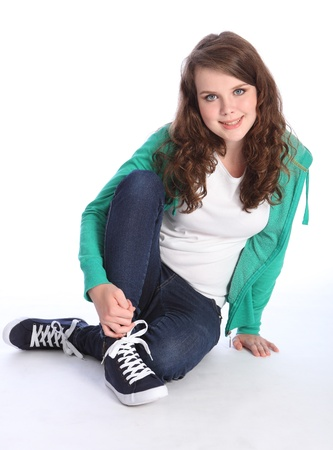 Beautiful blue eyes of a high school teenager girl with long brown hair wearing blue jeans and green jumper with big happy smile. Studio shot against white background. photo