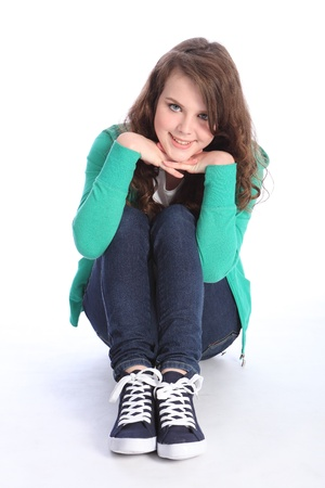 brown hair blue eyes: Beautiful blue eyes of a high school teenager girl with long brown hair wearing blue jeans and green jumper with big happy smile. Studio shot against white background.