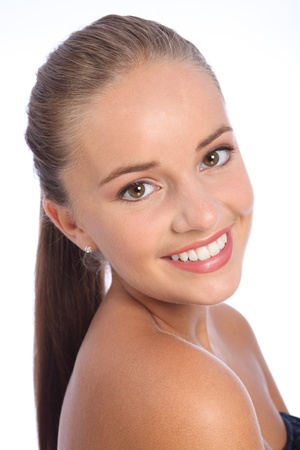 ponytail: Long brown hair ponytail and big happy smile of cheerful young caucasian teenager girl with beautiful brown eyes, taken against white background. Stock Photo