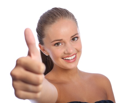 Thumbs up hand sign for positive success by a beautiful happy young teenager girl with big cheerful smile and happy brown eyes. Stock Photo