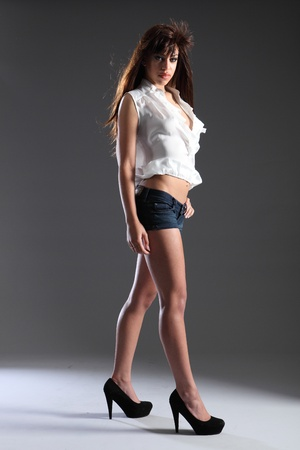afro caribbean: Tall slim beautiful young mixed race fashion model girl wearing denim shorts and white open top with stiletto heels, showing off long legs. Woman has long brown hair shot against grey background. Stock Photo