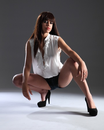 blue toned: Long legs in stilettos of a beautiful young mixed race fashion model girl wearing denim shorts and white open top, strikes a sexy pose crouching down shot against grey background.