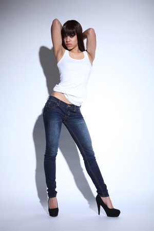 Beautiful young mixed race fashion model girl wearing blue denim jeans and white vest showing off flat stomach, standing in sexy pose with black stiletto heels. photo