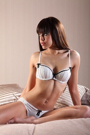 Beautiful young mixed race lingerie model woman with long brown hair, wearing sexy white knickers and bra set sitting up in bed staring at camera with green eyes. photo