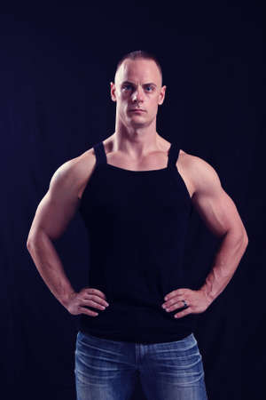 fit male with muscular biceps, wearing jeans and a black tank top, against a black background