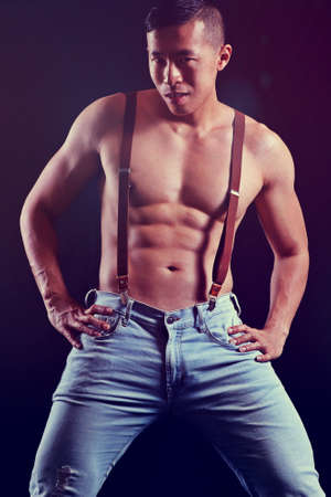 sexy Asian man with muscular chest and abs, shirtless, and wearing suspenders and jeans against a black background