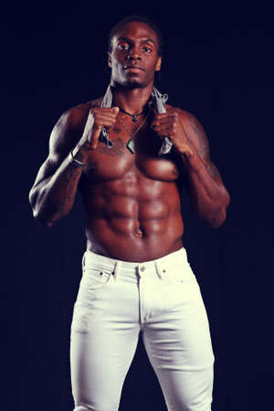 fit black male with super muscular abs, wearing white jeans, against a black background Stock Photo - 124934376