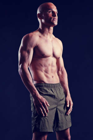 attractive male with muscular biceps, pecs, and abs, wearing gym shorts and against a black background