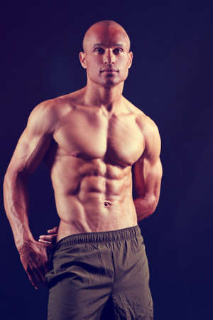 attractive man with muscular abs and chest, wearing gym shorts, and against a black background