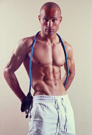 fit man with muscular abs with a resistance band around his neck against a cream background