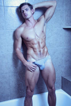 Attractive muscular man in the shower