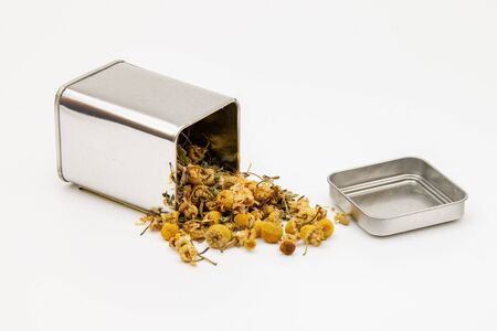 Isolated dried chamomile tea herbal infusion from a metal tin container