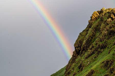 Colors of rainbow behind mountain ridge