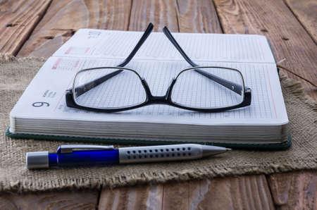 myopia: The black plastic glasses on the opened weekly. Myopia. Angle view.