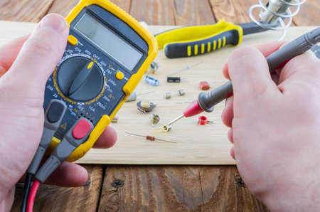 brazing: The workplace of serviceman. Hands holding the multimeter. Angle view.