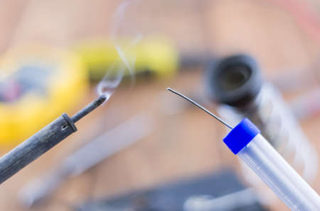 brazing: The incandescent soldering-iron and solder. Workplace. Angle view.