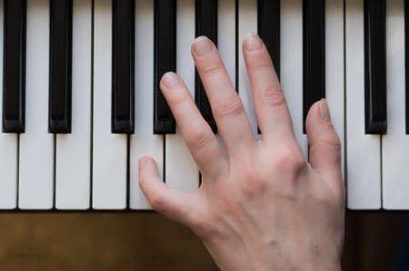 tocando piano: Mano de la mujer que juega m�sica de piano. Vista en �ngulo.