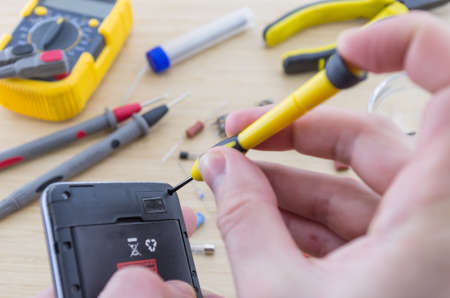 brazing: The workplace of serviceman. Smartphone repair with a screwdriver. Angle view.