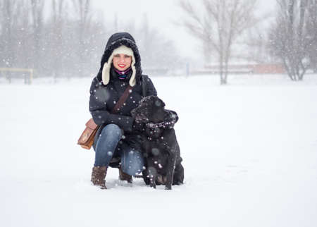 snowfield: The portrait of a girl with black dog on the snowfield