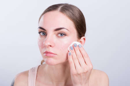 white washed: Beautiful young woman cleansing her face with cotton sponge Stock Photo