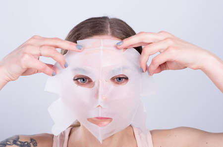 white washed: Beautiful young woman puts anti-aging mask on her face.