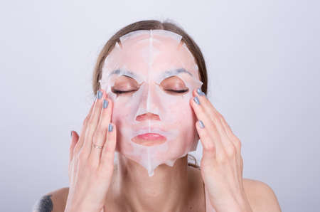Beautiful young woman puts anti-aging mask on her face.