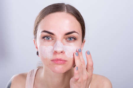white washed: Beautiful young woman puts scrub cream on her face.