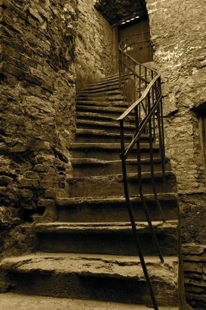 Old, shabby and curved stairs in a sepia version, which highlights the texture of the old building and bricks