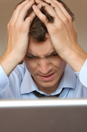 A frustrated businessman sitting at his laptop