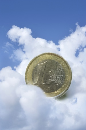 one euro coin suspended in the clouds