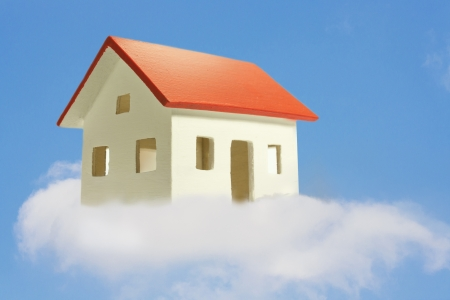 a model of a house rises in the clouds