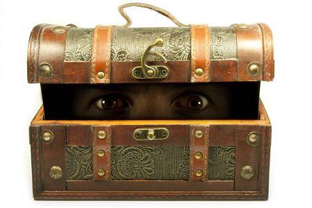 left eyes in dim light inside a trunk ajar Stock Photo