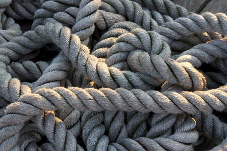 worn out rope and tangled on a deck of a ship Archivio Fotografico