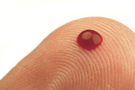 finger tip: small drop of blood on the tip of a finger