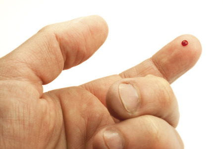 small drop of blood on the tip of a finger