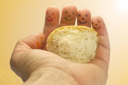 representation of sharing a piece of bread held in one hand Archivio Fotografico