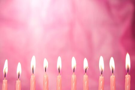 set of candles lit pink on pink background