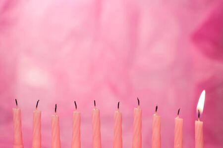pastel de cumpleaños: conjunto de velas de color rosa iluminada sobre fondo rosa Foto de archivo