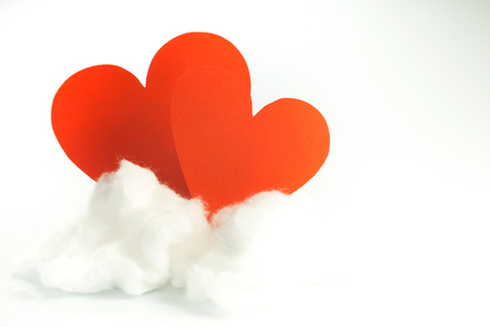 Red paper hearts on a white cloud of cotton