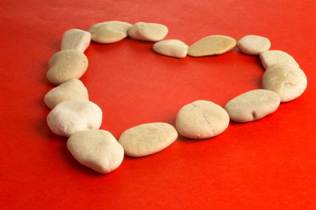 red paper heart and small pebbles of white river