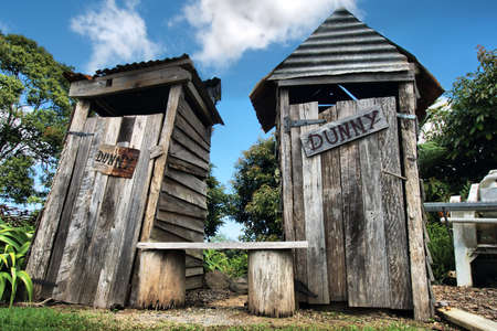 Classic country outhouse toilets with waiting area provided Stock Photo