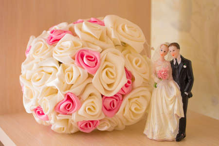 honeymooners: Wedding bouquet and white statue of honeymooners